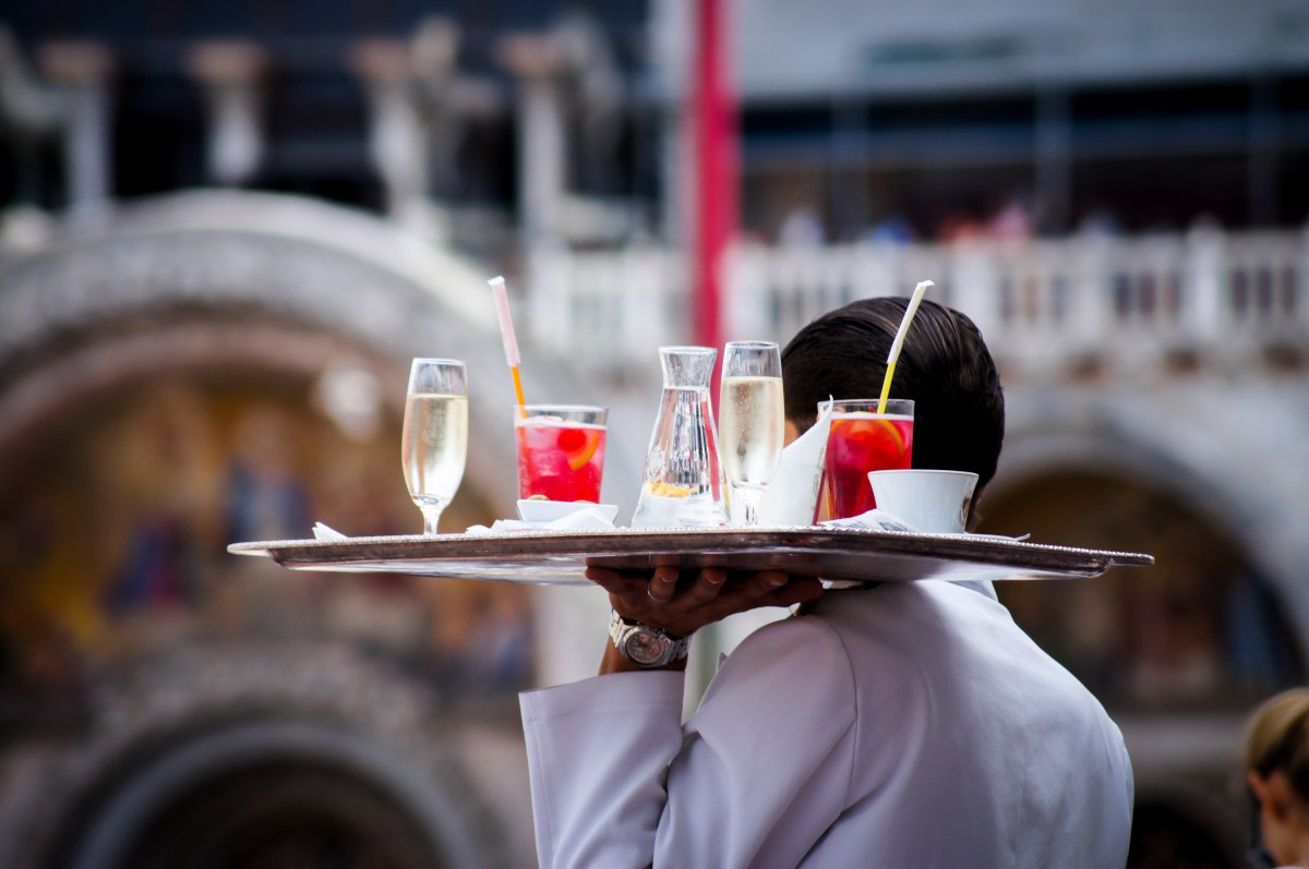 Waiter holding tray of beverages - Photo by Kate Townsend on Unsplash