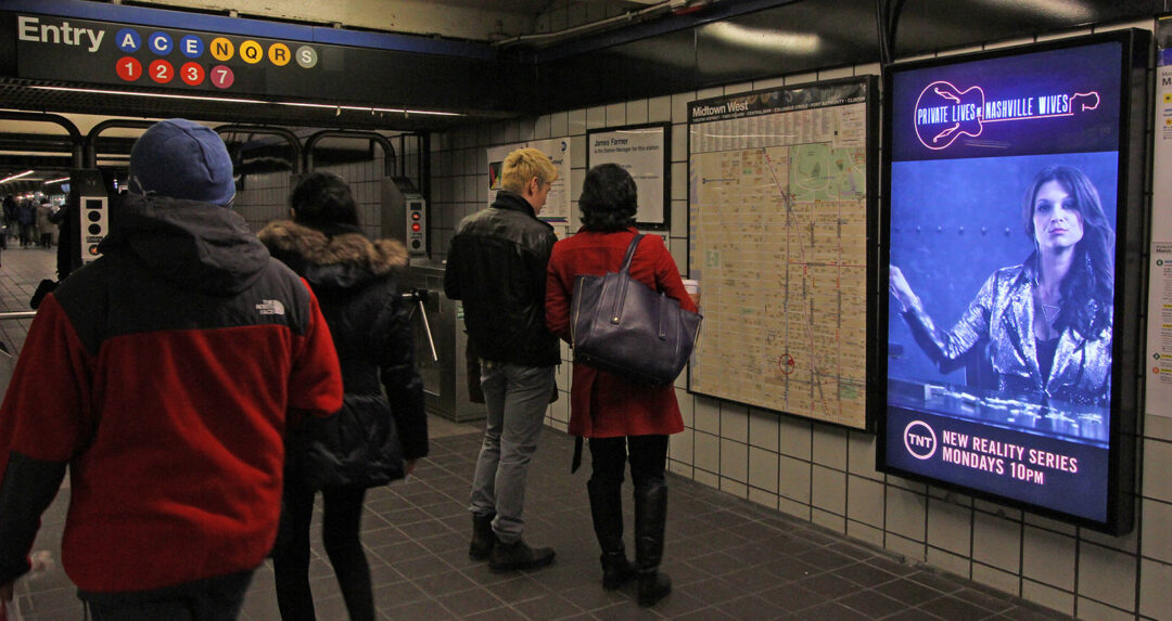 photo of people walking through a subway terminal with an ad displayed on an LCD screen on a wall